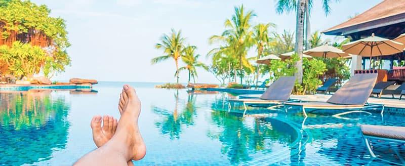 Foto de pernas cruzadas à beira da piscina.